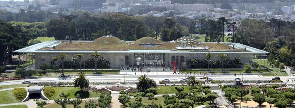 "The California Academy of Sciences, Golden Gate Park, San Francisco, California, as viewed from the tower of the de Young Museum (with the University of California, San Francisco Parnassus campus at the base of Mount Sutro in the distance). The building has a green roof. The three largest ""hills"" on the roof overlie the planetarium, swamp exhibit and rainforest exhibit (left to right). Photo credit: WolfmanSF. Licensed under CC BY-SA 3.0"