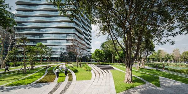 Approaching the new head office building, the combination of a preserved Banyan Tree and landscape form provides a complimentary setting for the new architecture. Image courtesy of Landscape Architects of Bangkok