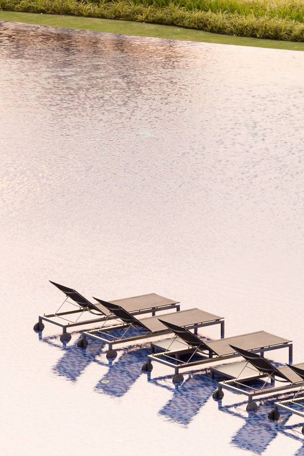 Shallow area in the pool is the perfect space for sun bathing. The lounge chairs appear as they are floating on the water.   Image credit: TROP: terrains + open space /  Wison Tungthunya