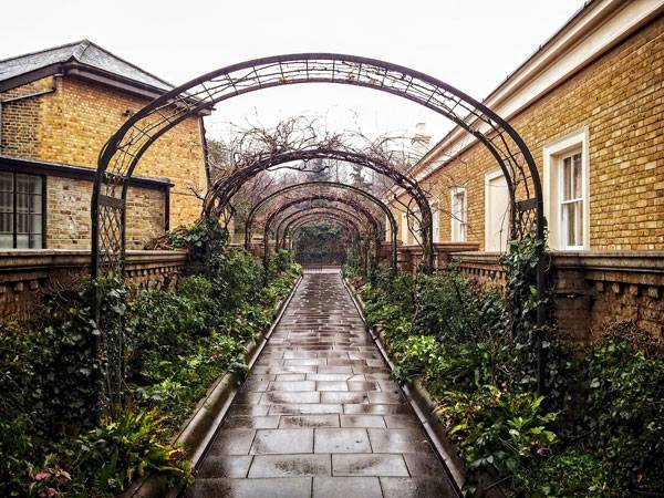 """Pergola walk, Garden of St John's Lodge, Regent's Park, London"" by Garry Knight from London, England - Leaving a Secret Garden. Licensed under CC BY-SA 2.0 via Wikimedia Commons - https://commons.wikimedia.org/wiki/File:Pergola_walk,_Garden_of_St_John%27s_Lodge,_Regent%27s_Park,_London.jpg#/media/File:Pergola_walk,_Garden_of_St_John%27s_Lodge,_Regent%27s_Park,_London.jpg"