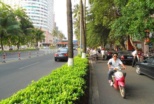 """""""Haikou street and bike lane - 01"""" by Anna Frodesiak - Own work. Licensed under CC0 via Commons - https://commons.wikimedia.org/wiki/File:Haikou_street_and_bike_lane_-_01.jpg#/media/File:Haikou_street_and_bike_lane_-_01.jpg"""