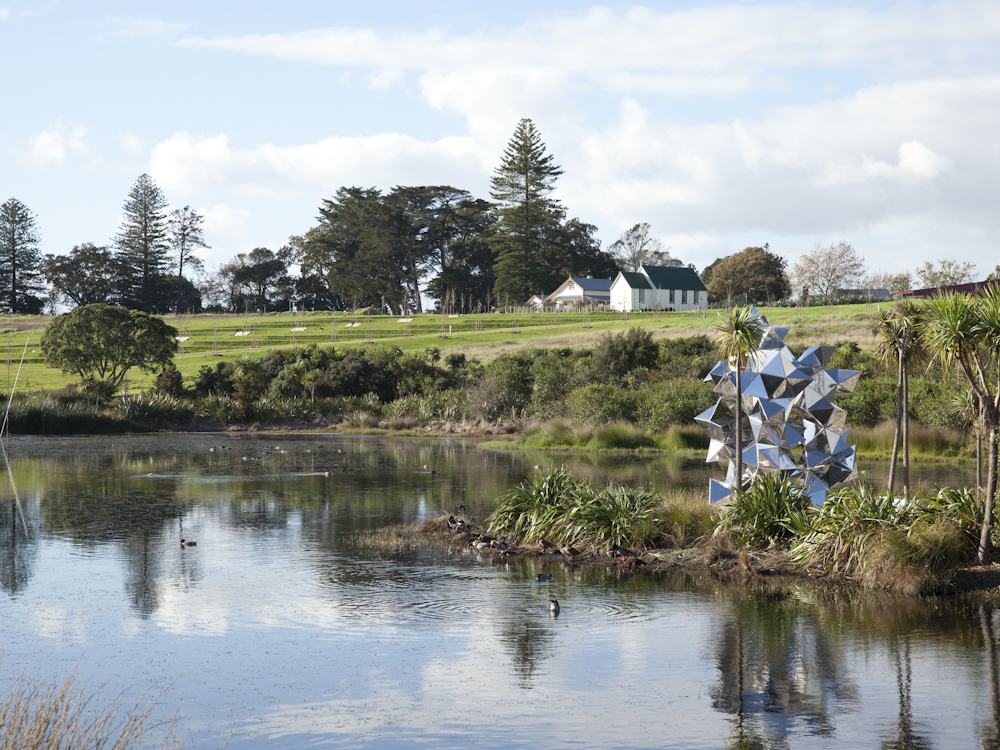 """Adjacent to Abbeville Estate, the Sculpture Park and Walk contains the project's primary stormwater-retention pond. Surfacedesign planted a corridor of trees to draw birds to the pond, away from the runways, and lowland edge plants for wildlife habitation. Island positioning showcases stainless-steel piece """"Fragmented Interactions"""" by artist Gregor Kregar. Photo courtesy Auckland International Airport, Ltd."""