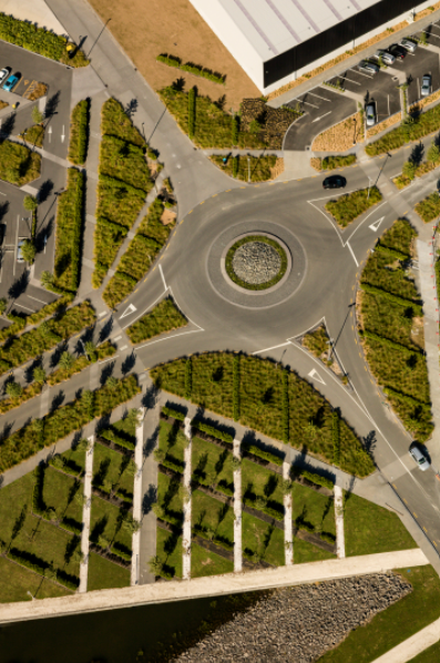 """The Landing Business Park features landscape design that incorporates delivery-truck-sized roundabouts inspired by Auckland's numerous volcanoes and the nearby Otuataua Stonefields Historic Reserve. Curbs and pavers use a custom volcanic-rock aggregate. Plantings reference hedgerows from European immigrants' planting practices. These lines extend to the """"parking orchards."""" Photo by Blake Marvin"""